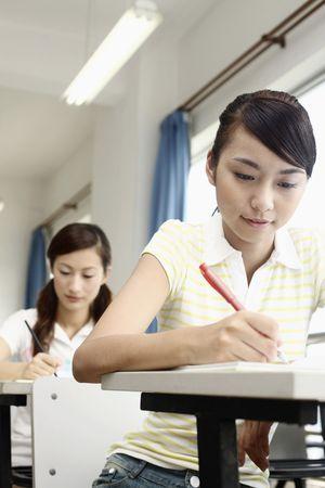 Young women writing in class