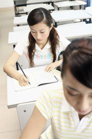Young women writing in class photo
