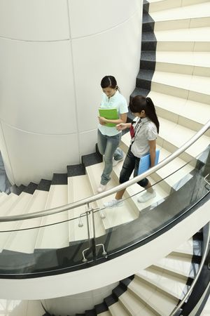 Young women chatting while walking down the stairs together photo