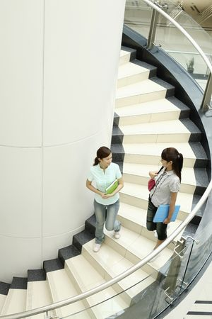 Young women chatting while walking down the stairs together Stock Photo - 4630833