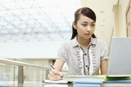 Young woman writing while using laptop Foto de archivo