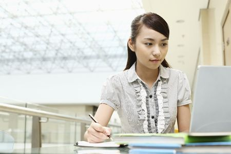 student writing: Young woman writing while using laptop Stock Photo