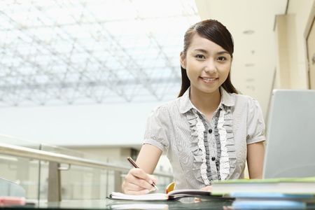 Young woman writing, smiling photo