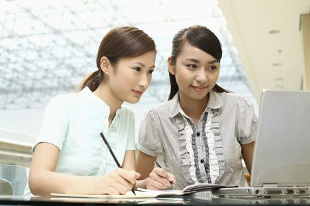 student writing: Young women writing while using laptop