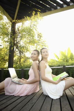 Young women sitting with their backs leaning against each other, smiling Stock Photo - 4631007