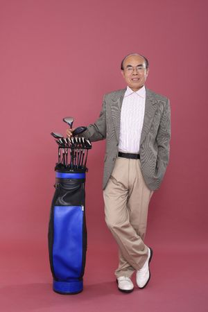 golf equipment: Senior man posing beside golf club bag