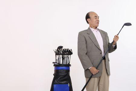 Senior man examining golf club photo