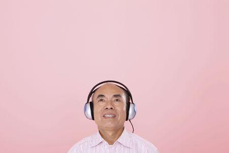 Senior man listening to headphones photo