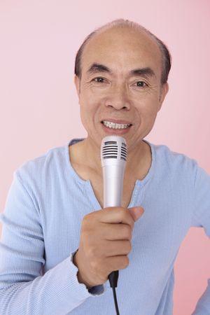 Senior man singing into microphone photo