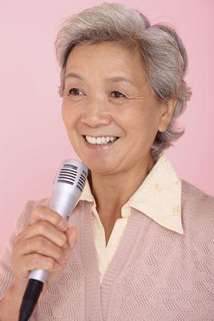 Senior woman singing into microphone
