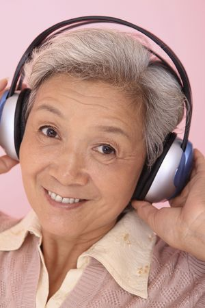 Senior woman listening to headphones photo