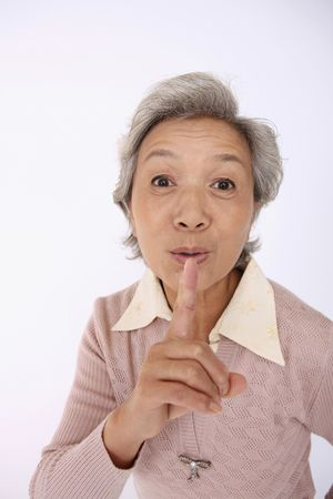 quiet adult: Senior woman with finger over her mouth