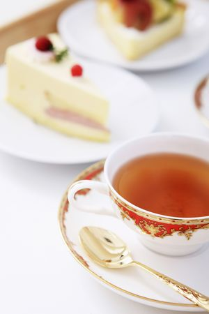 Cup of tea with slices of cake in the background