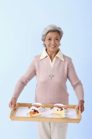 Senior woman holding a tray with tea, cake and tart photo