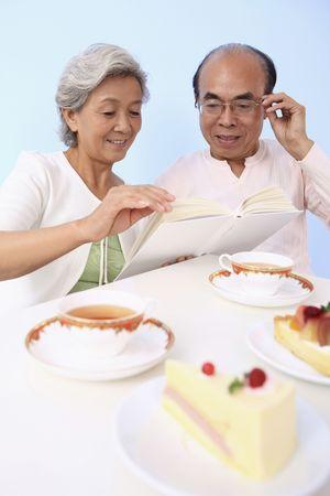 Senior man and woman reading book while enjoying cake and tea