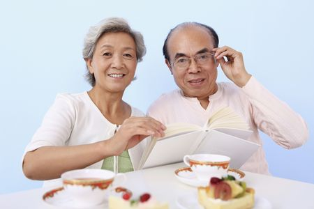 Senior man and woman reading book while enjoying cake and tea photo