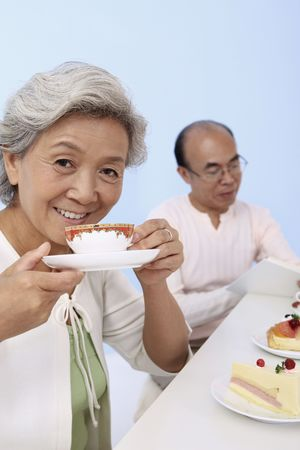 Senior woman enjoying tea with senior man reading in the background photo
