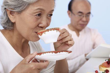 Senior woman enjoying tea with senior man reading in the background