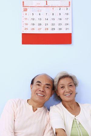 Senior man and senior woman sitting under calendar