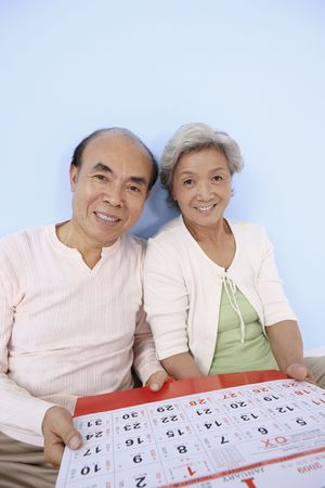 Senior man and senior woman holding calendar