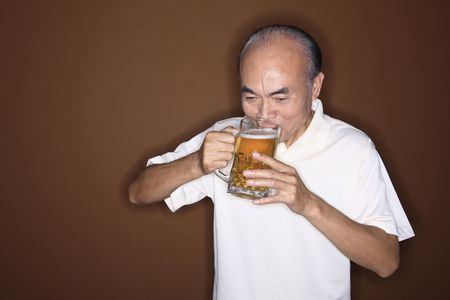 Senior man drinking beer photo