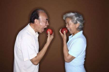 Senior woman and senior man eating apple photo