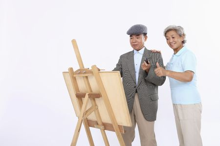 Senior woman complimenting senior man's art work Stock Photo - 4636476