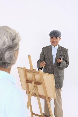 Senior man painting senior woman's portrait Stock Photo - 4636212