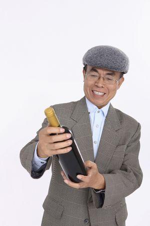 Senior man holding wine bottle photo