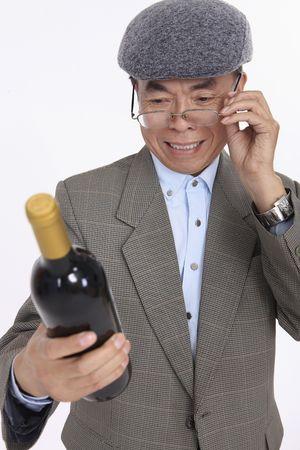 Senior man holding wine bottle, reading its label photo