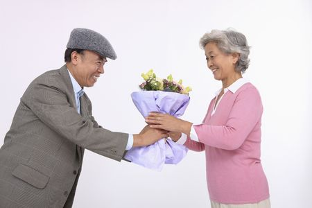 Senior man giving senior woman a bouquet of flowers photo