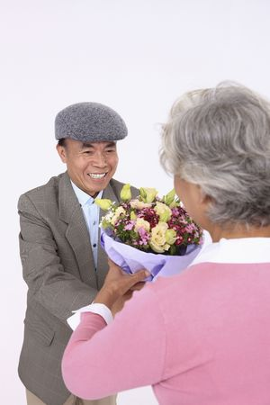 Senior man giving senior woman a bouquet of flowers photo