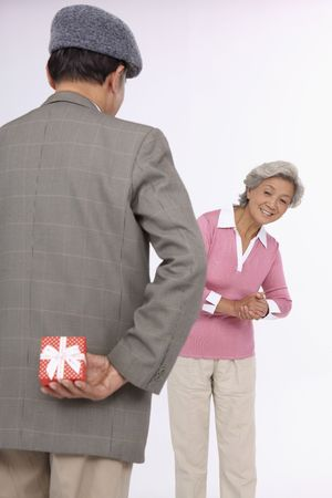 Senior man holding gift for senior woman behind his back photo