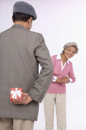 Senior man holding gift for senior woman behind his back photo