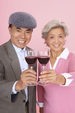 Senior man and senior woman toasting wine photo