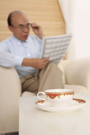 reading material: Senior man reading newspaper, focus on cup in the foreground Stock Photo