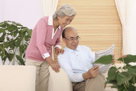 Senior man showing senior woman an article in the newspaper Stock Photo