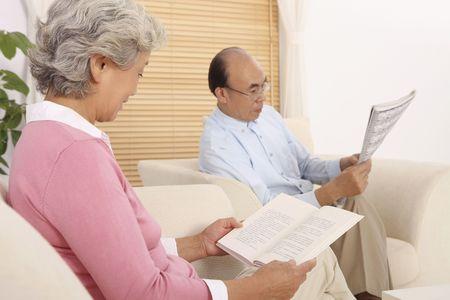Senior woman reading book while senior man is reading newspaper photo