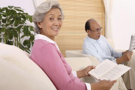 reading material: Senior woman smiling at camera while senior man is reading newspaper Stock Photo