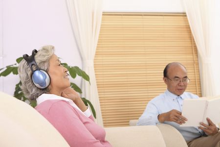 Senior woman listening to headphones, senior man reading book photo