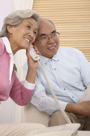 Senior man and senior woman listening to the telephone together Stock Photo
