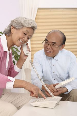 Senior woman making a telephone call, senior man watching her Stock Photo