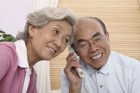 Senior man talking on the phone, senior woman listening at the side photo