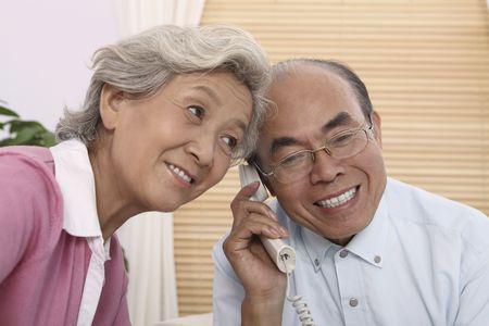 Senior man talking on the phone, senior woman listening at the side