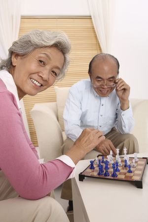 Senior man and senior woman playing chess, senior woman looking at the camera