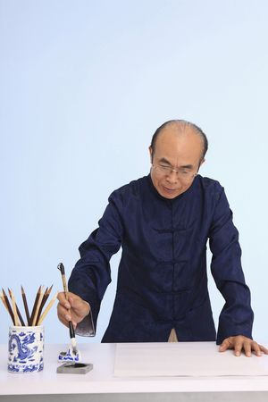 Senior man in traditional clothing writing calligraphy photo