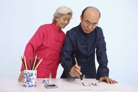 Senior woman observing senior man writing calligraphy photo
