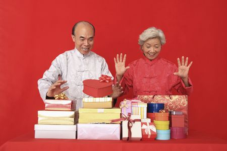 Senior man and senior woman looking excited at gift boxes and paper bags photo