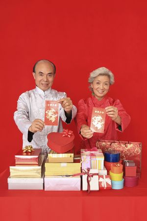 Senior man and senior woman holding red packets and smiling photo