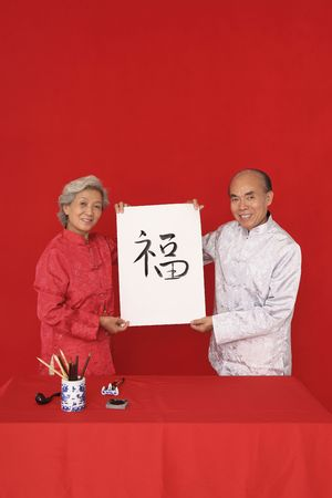 Senior man and senior woman holding up a paper with chinese word written on it photo